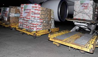 """In this photo released by the Syrian official news agency SANA, Iranian aid supplies are seen unloaded from a plane at a Damascus airport in Syria on March 15, 2012. The Arabic words on the Iranian flags which attached on the boxes read: """"Tribute of love and loyalty from the people of Iran to the dear Syrian people, left, and A gift from Islamic Iran to lofty Syria, right."""" (Associated Press/SANA)"""