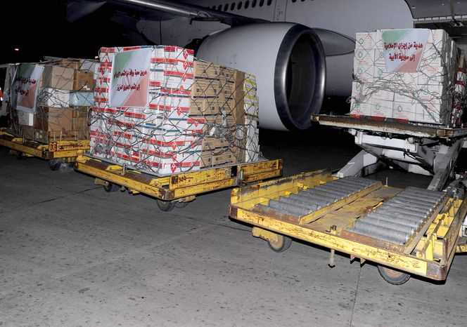 "In this photo released by the Syrian official news agency SANA, Iranian aid supplies are seen unloaded from a plane at a Damascus airport in Syria on March 15, 2012. The Arabic words on the Iranian flags which attached on the boxes read: ""Tribute of love and loyalty from the people of Iran to the dear Syrian people, left, and A gift from Islamic Iran to lofty Syria, right."" (Associated Press/SANA)"