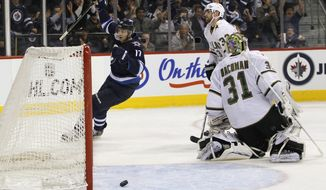 Winnipeg Jets' Eric Fehr (17) celebrates his goal on Dallas Stars' goaltender Richard Bachman during second period in Winnipeg, Manitoba, on Wednesday, March 14, 2012. (AP Photo/The Canadian Press, John Woods)