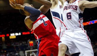 Washington Wizards' John Wall (2) runs into Atlanta Hawks' Kirk Hinrich (6) on his way to the basket during the first half in Atlanta, Friday, March 16, 2012. (AP Photo/Rich Addicks)