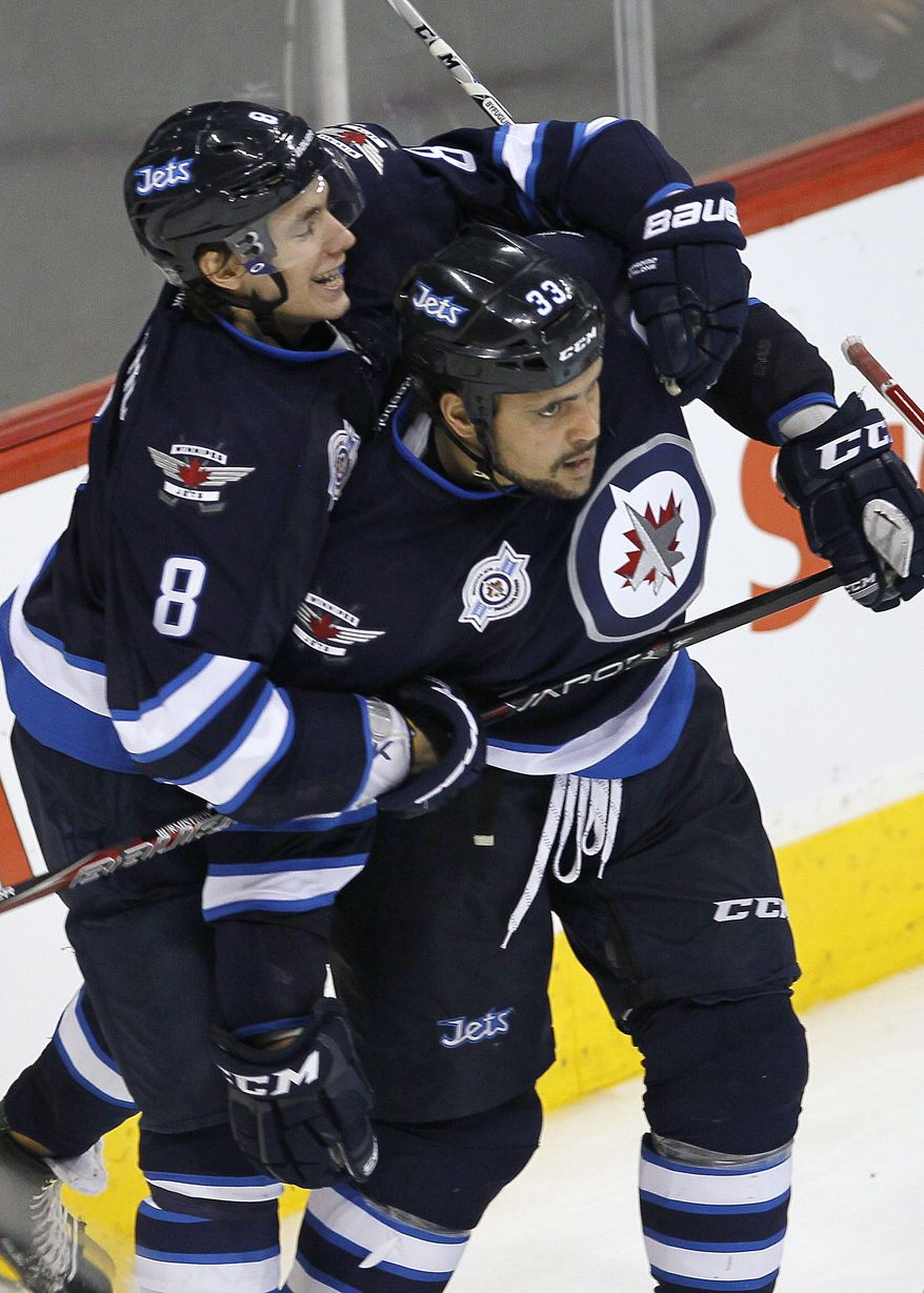 Winnipeg Jets' Alexander Burmistrov (8) and Dustin Byfuglien (33) celebrate Byfuglien's game-winning goal against the Washington Capitals in Winnipeg, Manitoba, on Friday, March 16, 2012. (AP Photo/The Canadian Press, John Woods)