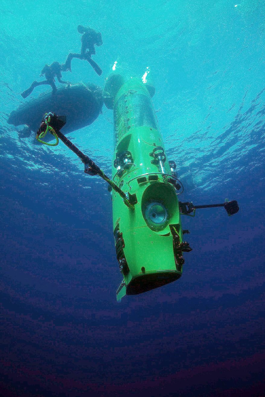 Director James Cameron will be taking the cramped, almost-form-fitting Deepsea Challenger submersible (top) seven miles down into the Mariana Trench in the western Pacific. (National Geographic via Associated Press)