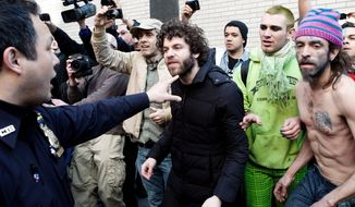 An Occupy Wall Street demonstrator is directed to step back from the scene of an arrest Saturday in New York by a police officer, after a march marking six months since the movement's founding. Protesters lack consensus on what the group's focus should be going forward. (Associated Press)