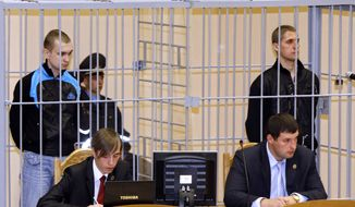 ** FILE ** Belarusians Dmitry Konovalov (left) and Vladislav Kovalev stand in a defendant's cage during a court session in Minsk, Belarus, on Thursday, Sept. 15, 2011. (AP Photo/Sergei Grits, File)