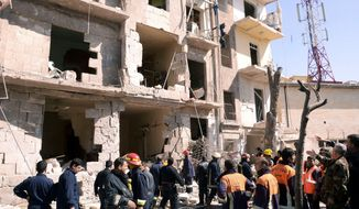 Rescue teams investigate the scene of an explosion in Aleppo, Syria, on Sunday, March 18, 2012. (AP Photo/SANA)