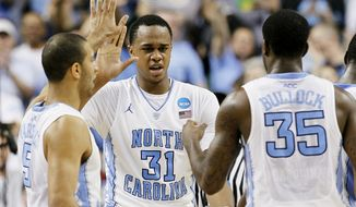 North Carolina's Kendall Marshall, John Henson (31) and Reggie Bullock (35) react during the second half of an NCAA tournament third-round college basketball game against Creighton in Greensboro, N.C., Sunday, March 18, 2012. North Carolina won 87-73. (AP Photo/Gerry Broome)