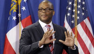 Actor Tyler Perry takes the stage to introduce President Obama during a fundraiser at Mr. Perry's film studio on Friday, March 16, 2012, in Atlanta. (AP Photo/David Goldman)
