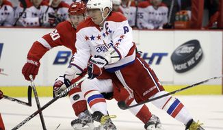 Washington Capitals left wing Alex Ovechkin (8) controls the puck in front of Detroit Red Wings left wing Drew Miller during the second period of an NHL game in Detroit, Monday, March 19, 2012. The Capitals won 5-3. (AP Photo/Carlos Osorio)
