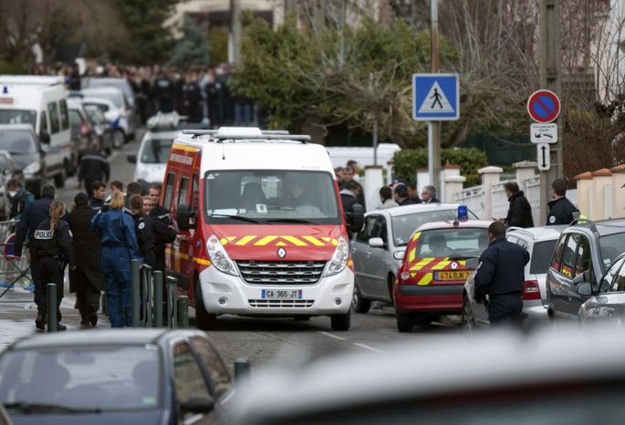 Police officers and firefighters gather near a Jewish school in Toulouse, France, on Monday, March 19, 2012, after a gunman killed a man, his two sons and one other child outside the school. (AP Photo/Bruno Martin)