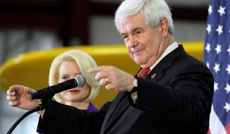 """Newt Gingrich, with wife Callista, speaks at the airport of Lake in the Hills, Ill., Thursday. The former House speaker sounds less hawkish on foreign-policy matters. """"Instability rather than aggression is the great threat,"""" he recently said of North Korea. (Associated Press)"""