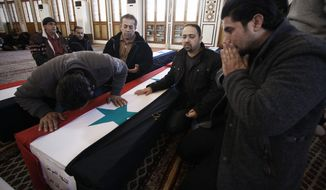 Mourners attend the funeral of victims of a suicide bombing in Damascus, Syria, on Sunday, March 18, 2012. (AP Photo/Muzaffar Salman)