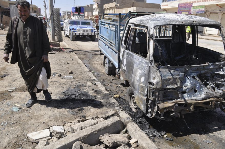 A man stands at the scene of a car-bomb attack in Ramadi, 70 miles west of Baghdad, on Tuesday, March 20, 2012. Officials say attacks across Iraq have killed and wounded scores of people in a spate of violence that was expected in the days before Baghdad hosts the Arab world's top leaders. (AP Photo)