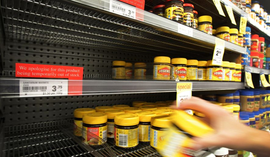 A customer takes a jar of Vegemite from the shelf next to an empty section where Marmite should be stocked in a supermarket in Auckland, New Zealand, on Tuesday, March 20, 2012. (AP Photo/New Zealand Herald, Sarah Ivey) ** FILE **