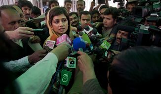 ** FILE ** Pakistani Foreign Minister Hina Rabbani Khar talks to the media as she leaves a joint session of Parliament in Islamabad on Tuesday, March 20, 2012. A parliamentary commission demanded an end to American drone attacks inside Pakistan and an apology for deadly U.S. airstrikes in November, as part of proposed new terms in the country's troubled relations with the U.S. (AP Photo/Anjum Naveed)