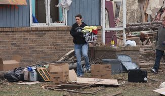 A woman retrieves items from a home in Bailey Yard, Neb., west of North Platte, after a tornado hit the area on Sunday, March 18, 2012. The National Weather Service rated the twister an EF3, with top winds of 165 mph. (AP Photo/The Telegraph, Joe Volcek)