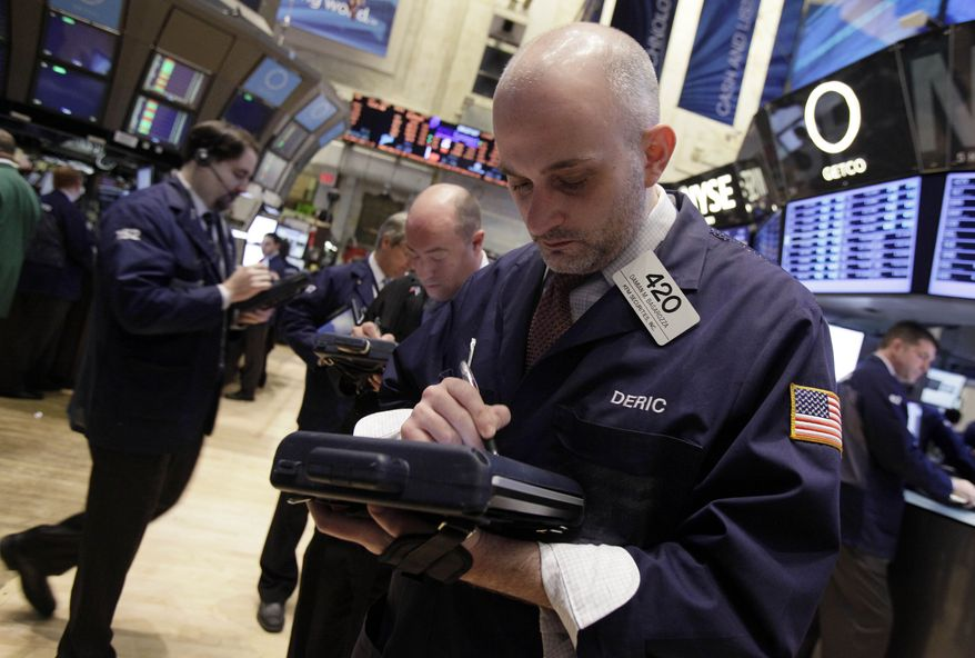 Damian Bagarozza (right) works with fellow traders on the floor of the New York Stock Exchange on Monday, March 19, 2012, in New York. (AP Photo/Richard Drew)
