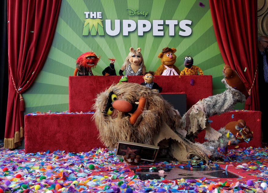 Jim Henson's puppet character Sweetums the ogre shows off the star with other Muppets characters as they are honored on the Hollywood Walk of Fame in Los Angeles on Tuesday. Kermit, Miss Piggy and Fozzie Bear were also on hand for the honor. (Associated Press)