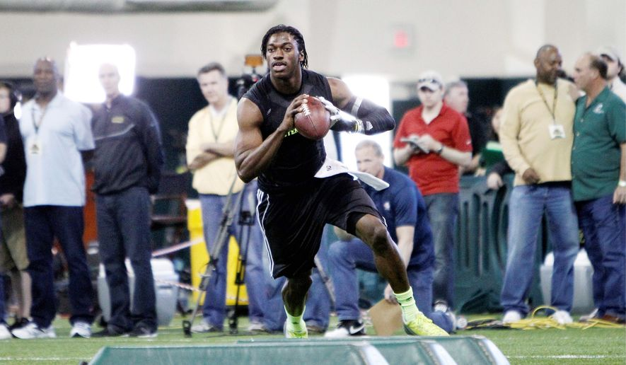 Heisman Trophy-winning quarterback Robert Griffin III runs a footwork drill Wednesday during Baylor's pro day workout in Waco, Texas. Redskins coach Mike Shanahan, owner Daniel Snyder, general manager Bruce Allen and offensive coordinator Kyle Shanahan were among those in attendance. (Associated Press)