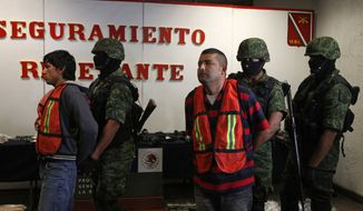 """Mexican army soldiers take away Jose Guadalupe Serna Padilla (center), aka """"El Zopilote,"""" or """"the Vulture,"""" and his alleged accomplice Oscar Pozos Jimenez (left) during a presentation to the press in Zapopan, on the outskirts of Guadalajara, Mexico, on Sunday, March 18, 2012. (AP Photo/Bruno Gonzalez)"""