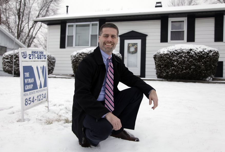 ** FILE ** In this Feb. 14, 2012, photo, Paul Wyman, a realtor and Republican County Commissioner, poses outside a foreclosed home for sale in Kokomo, Ind. (AP Photo/Michael Conroy)