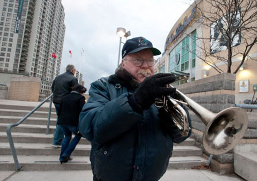 Local busker Brian Grillis plays his trumpet as fans trickle into the John Labatt Centre to watch their hometown junior hockey club, the London Knights, play against the visiting Ottawa 67's, in London, Ontario, Canada on Saturday March 3, 2012. Grillis has become a staple for arriving fans, missing only a handful of games since the team started playing at the downtown arena in 2002.  (Craig Glover/Special to The Washington Times)