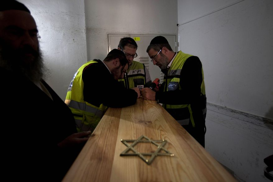 Israeli burial officials at a morgue in Jerusalem prepare the coffins of the Toulouse shooting victims for their funeral on Wednesday, March 21, 2012. (AP Photo/Oded Balilty)