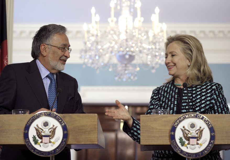 Secretary of State Hillary Rodham Clinton (right) extends her hand to Afghan Foreign Minister Zalmai Rassoul during a press briefing following their meeting at the State Department in Washington on Wednesday, March 21, 2012. (AP Photo/Cliff Owen)