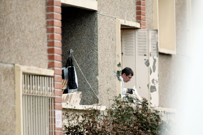 A French police officer inspects a window at Mohamed Merah's apartment in Toulouse on Thursday after the Islamic extremist, wanted in the deaths of three paratroopers, three Jewish schoolchildren and a rabbi, died in a shootout with police. He was shot in the head as he jumped out of his apartment window after a 32-hour standoff. (Associated Press)