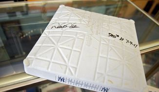 "The base that New York Yankees Derek Jeter signed after getting his 3,000th hit lays on the counter of ""Robbie's First Base"" in Lutherville, Md. (Mary F. Calvert/Special to The Washington Times)"