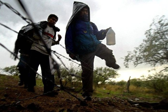 Illegal immigrants easily step over a fallen barbed-wire fence between Mexico and the United States near the town of Sasabe, Mexico, in 2004. The number of apprehensions of illegal border-crossers is down while the number of deaths in the desert is high. (Associated Press)