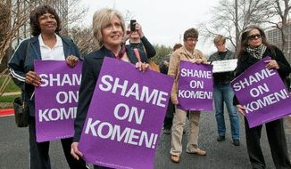 A small group of women protest Feb. 7 outside the Susan G. Komen for the Cure headquarters in Dallas in the immediate aftermath of the breast cancer charity's short-lived cutoff of funding to Planned Parenthood. Several high-ranking executives have since left or intend to leave the organization. (Associated Press)
