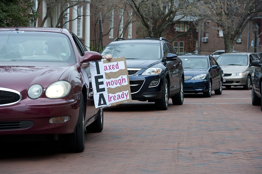 "A driver holds a ""Taxed Enough Already"" sign out of his car as he and a handful of other cars drive around the State House in Annapolis, Md., on Thursday, March 22, 2012, honking their horns in protest of new and increased taxes in the state of Maryland. At least two drivers were ticketed for illegal use of horn, a $60 fine. (Barbara L. Salisbury/The Washington Times)"