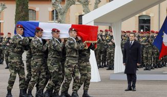 ** FILE ** French President Nicolas Sarkozy stands by soldiers carrying a coffin during a ceremony in Montauban, southwestern France, on March 21, 2012, to pay homage to the three soldiers killed by a suspect claiming al Qaeda links and also suspected in the killings of three Jewish children and a rabbi. (Associated Press)