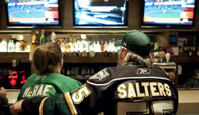 London Knights hockey fan Dylan Medd, right, sits with his arm around his wife, Angie Brereton, while drinking a beer and watching sports at Kingwest Bar and Grill before walking across the street for a game in London, Ontario, Canada on Friday March 2, 2012. (Craig Glover/Special to The Washington Times)