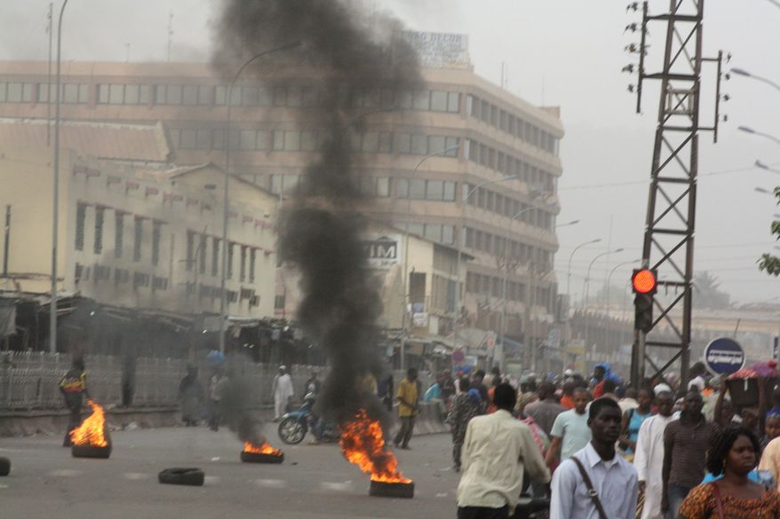 Civilians walk past tires set afire in support of mutinying soldiers in Bamako, Mali, on Wednesday, March 21, 2012. (AP Photo/Harouna Traore)