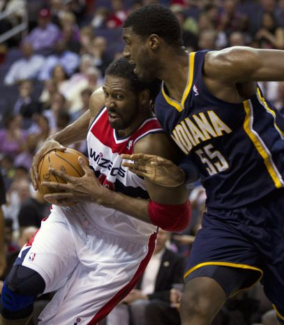 Washington Wizards center Nene, left, of Brazil, drives to the basket against Indiana Pacers center Roy Hibbert (55) during the first half of an NBA basketball game on Thursday, March 22, 2012, in Washington. (AP Photo/Evan Vucci)