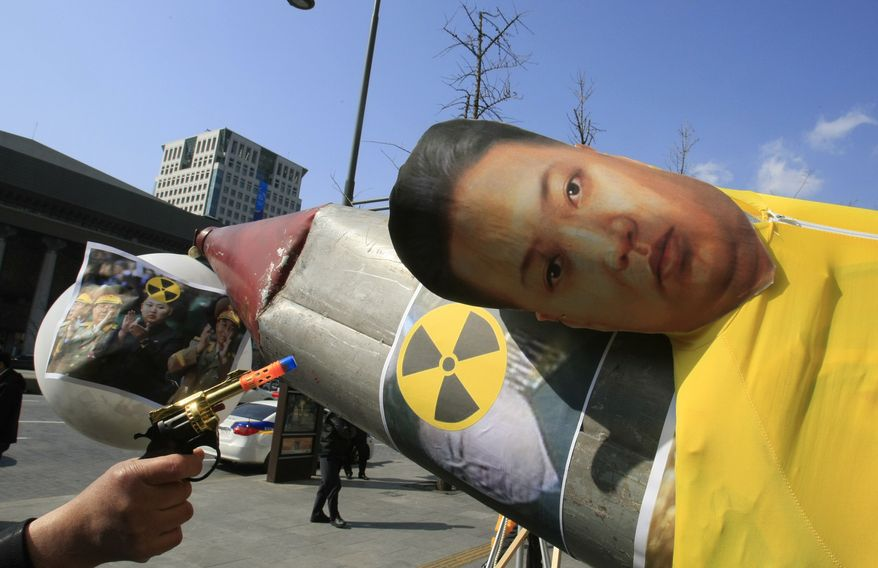 A South Korean protester aims a toy gun at an effigy of North Korean leader Kim Jong-un, which is set on a mock North Korean missile during an anti-North Korea rally denouncing North's plan to launch a long-range rocket in Seoul on March, 20, 2012. (Associated Press)