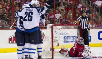 Washington Capitals goalie Michal Neuvirth lies on the ice as Winnipeg Jets center Bryan Little, right wing Blake Wheeler and left wing Andrew Ladd celebrate Little's during the second period Friday, March 23, 2012, in Washington. (AP Photo/Evan Vucci)