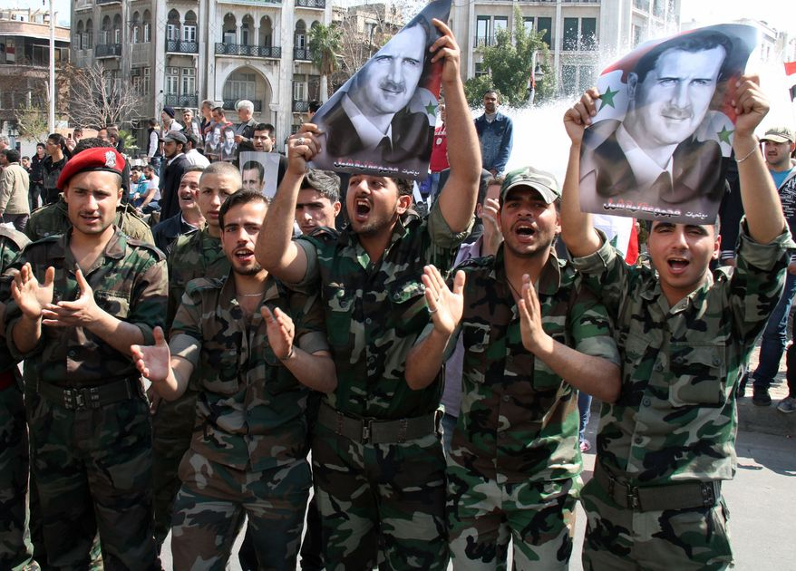 Syrian Army soldiers shout slogans and hold up portraits of Syrian President Bashar Assad during a pro-regime rally in Damascus, Syria, on March 23, 2012. (Associated Press)