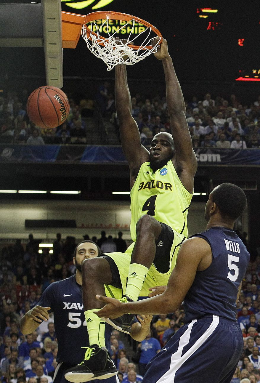 Baylor's Quincy Acy dunks the ball as Xavier's Dezmine Wells, right, and Andre Walker look on during the second half of an NCAA tournament South Regional semifinal Friday, March 23, 2012, in Atlanta. (AP Photo/John Bazemore)