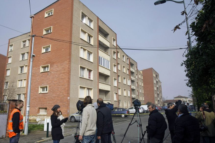 Members of the media stand in front of Mohamed Merah's apartment building in Toulouse, France, Friday March 23, 2012. Mohamed Merah, who boasted of killing seven people to strike back at France died on Thursday after being shot in the head by police as he jumped out of his apartment after a fierce gunfight with police, authorities said. (AP Photo/Remy de la Mauviniere)