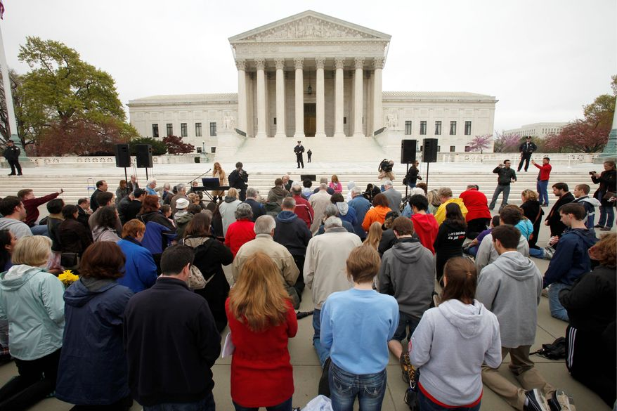 """Members of Christian faith organizations kneel in prayer in front of the Supreme Court in Washington on Sunday as part of """"Encircle the Court in Prayer"""" on the eve of the Supreme Court arguments on President Obama's health care legislation. (Associated Press)"""