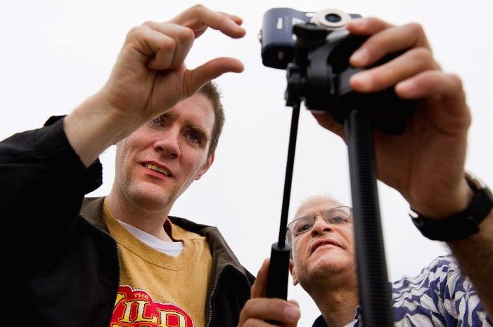Staff member Rene Gonzales (right) helps Matt take photographs before Matt returned to the computer lab at the Community Services for Autistic Adults and Children in Montgomery Village for editing. (Andrew Harnik/The Washington Times)