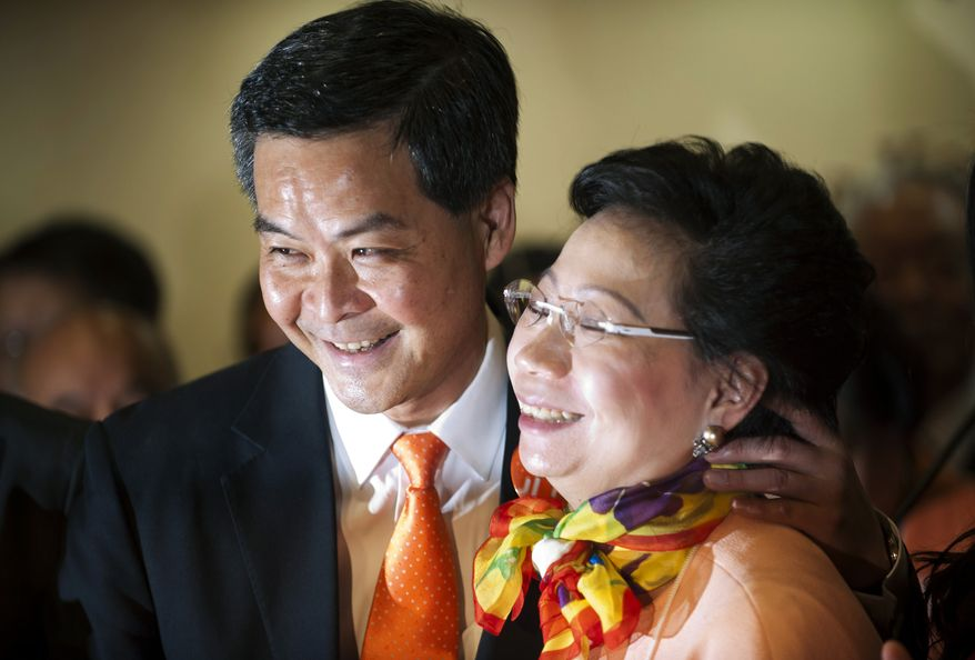 Leung Chun-ying (left) and his wife, Regina, celebrate his victory in the chief executive election on Sunday, March 25, 2012, in Hong Kong. (AP Photo)