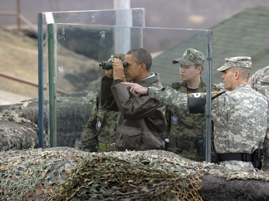 **FILE** President Obama looks through binoculars toward North Korea from Observation Post Ouellette in the Demilitarized Zone, the tense military border between the two Koreas, in Panmunjom, South Korea, on March 25, 2012. With Mr. Obama is Lt. Col. Ed Taylor (right), commander of the U.N. Command Security Battalion-Joint Security Area. (Associated Press)