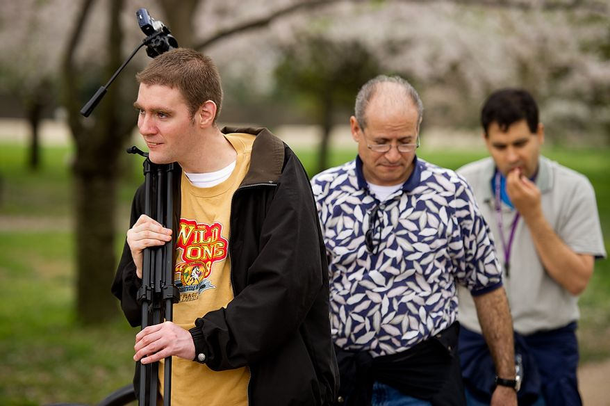 "Autistic adults Matt D., left, and Jimmie R., right, with Community Services for Autistic Adults and Children, based in Montgomery Village, Md., are accompanied by staff member Renee Gonzales, center, as they take photographs of the Cherry Blossoms along the Tidal Basin, Washington, D.C., Wednesday, March 21, 2012. The ""InFocus Project†is a way for adults with autism to develop forms of self expression and social skills while producing work that has been featured in art shows, given to donors to C.S.A.A.C., and sold on an online store. (Andrew Harnik/The Washington Times)"
