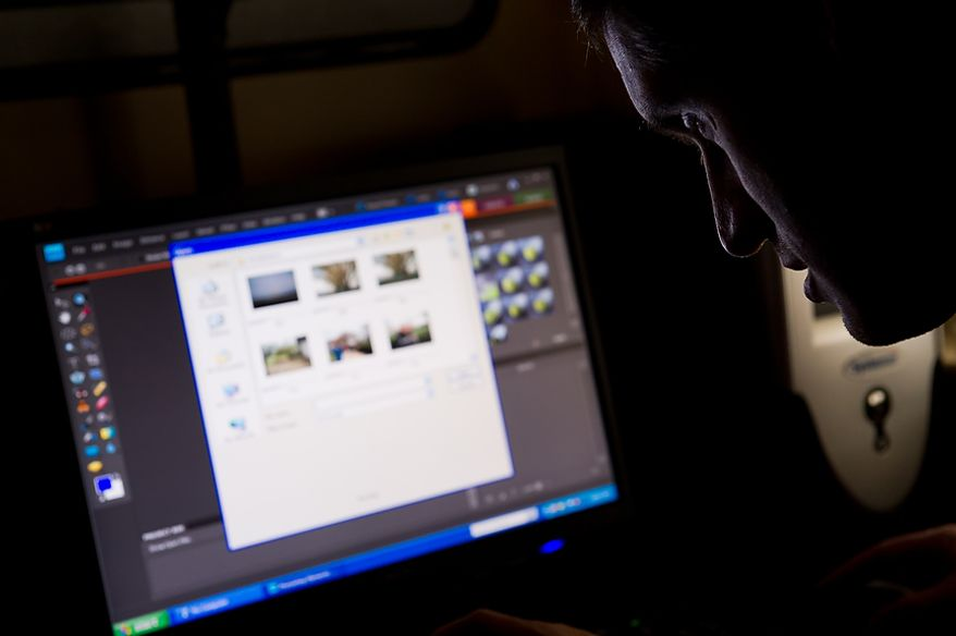 """Autistic adult James L. edits his photographs of the Cherry Blossoms taken along the Tidal Basin at a computer lab at the Community Services for Autistic Adults and Children, Montgomery Village, Md., Thursday, March 22, 2012. James is part of the """"InFocus Project†which helps adults with autism to develop forms of self expression and social skills while producing work that has been featured in art shows, given to donors to C.S.A.A.C., and sold on an online store. (Andrew Harnik/The Washington Times)"""