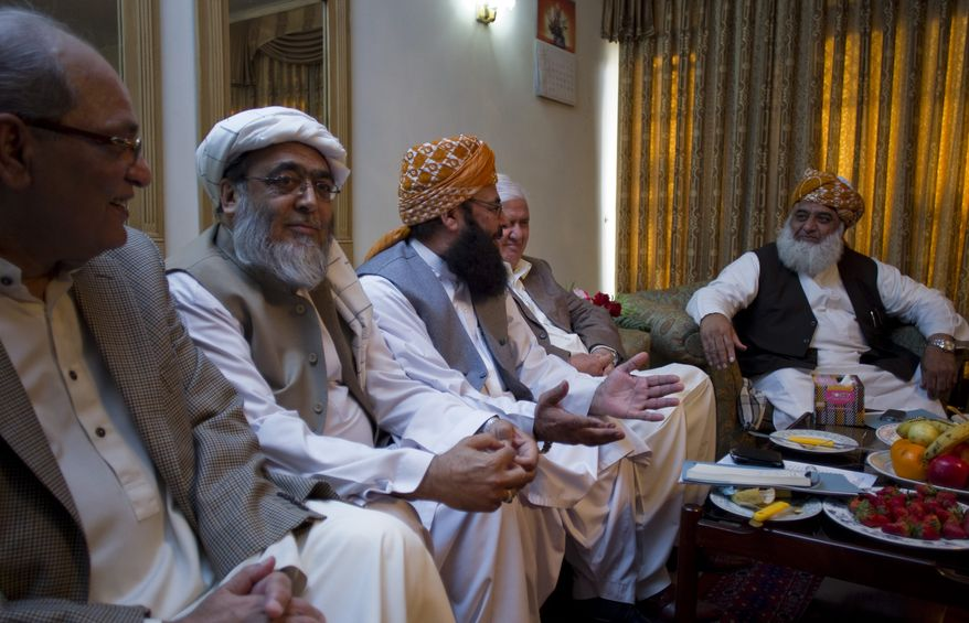 Maulana Fazal-ur-Rehman (right), chief of the Pakistani religious party Jamiat Ulema-e-Islam, heads a meeting of opposition leaders on Saturday, March 24, 2012, in Islamabad to discuss strategy for the forthcoming Parliament debate on the terms of re-engagement with United States. (AP Photo/B.K. Bangash)