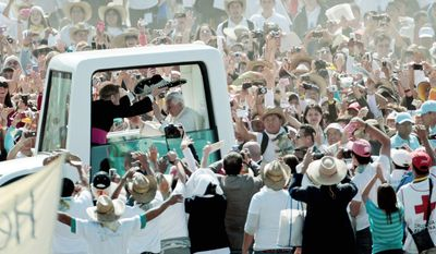 The crowd cheers as Monsignor Georg Gaenswein, left, puts a Mexican sombrero on Pope Benedict's XVI head as they arrive in  Parque del Bicentenario to celebrate a Sunday Mass. (AP Photo/Gregorio Borgia)