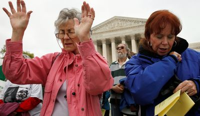 """Joan Schnabel of Annapolis, Md., left, and Marge Groetsch of Front Royal, Va., pray in front of the Supreme Court as part of """"Encircle the Court in Prayer,"""" an event led by Christian faith organizations. (AP Photo/Jacquelyn Martin)"""